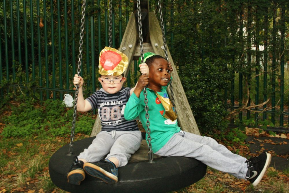 Two children sharing a swing at Hayward Adventure Playground.